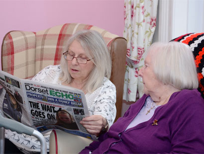 Carer reading to resident