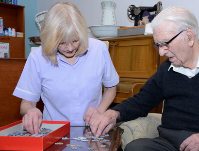 Resident doing puzzle with Carer